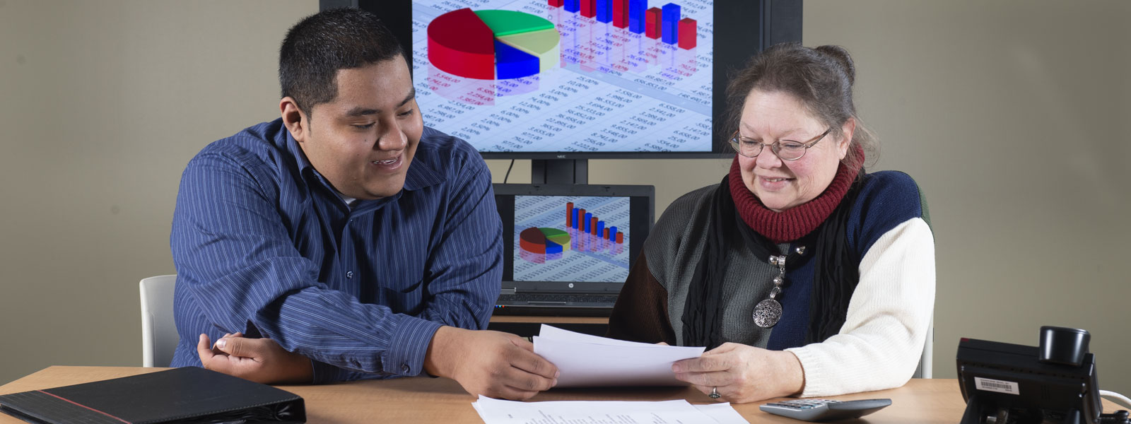 Two people sitting at a desk going over document together with diagram on projection screen in background.