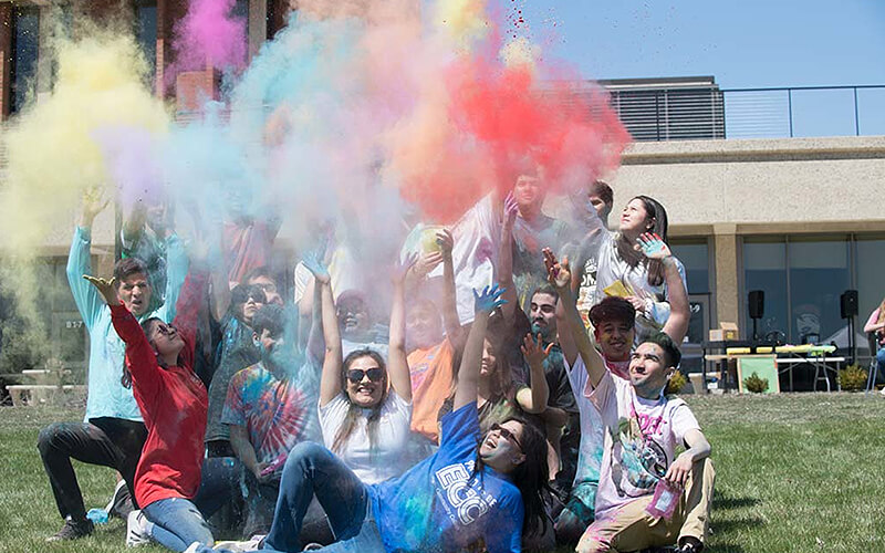 Group of students throwing colored chalk into the air.