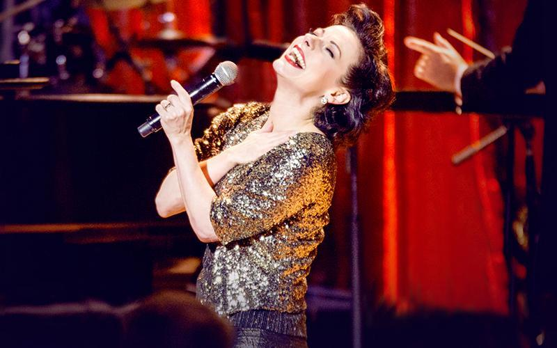 Angela Ingersoll sings into a microphone while portraying Judy Garland