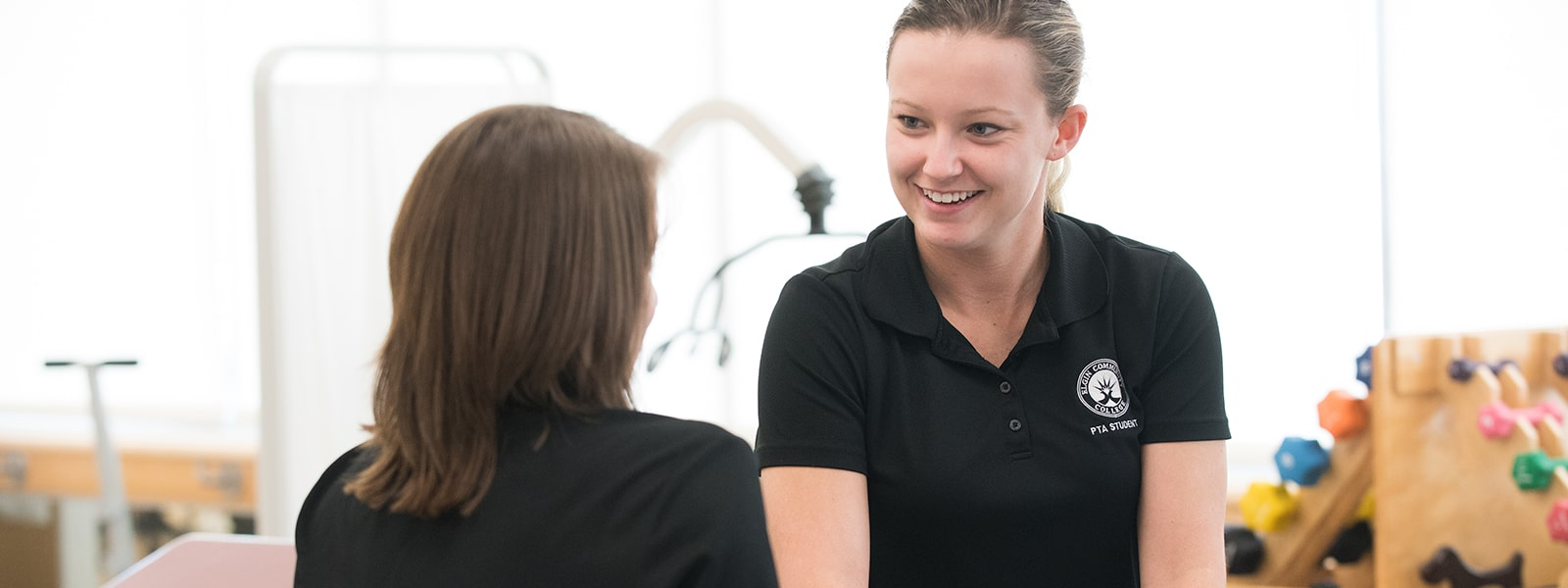 A Physical therapist assistant student working with a client.