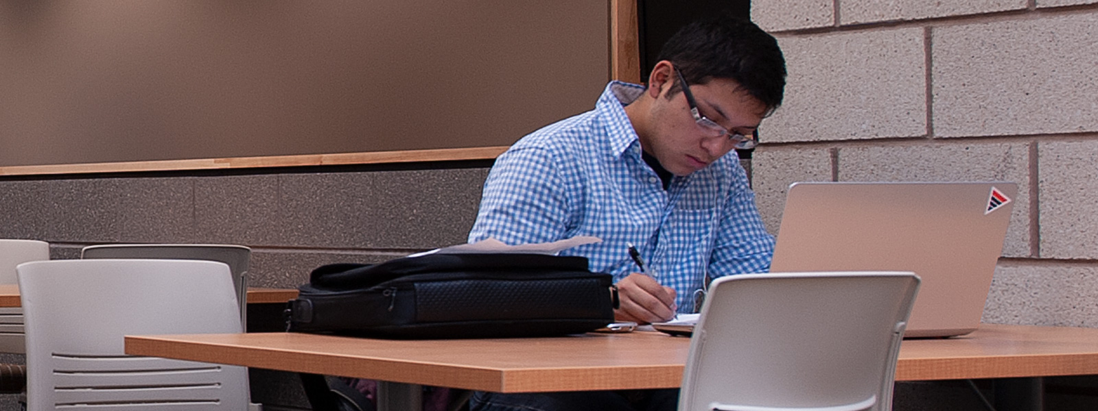 Student at desk working on computer doing work.